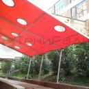 Тентовый навес односкатного исполнения в качестве места для курения. Тентовая кровля выполнена из красного материала с прозрачными мягкими ПВХ вставками в качестве декоративного оформления и световых окон.