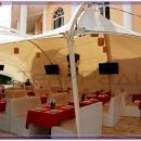 Прозрачная тентовая кровля конструкции летнего кафе создает праздничное и светлое ощущение под тентовым навесом.